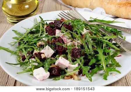Salad from roasted beets arugula cheese feta and walnuts. Horizontal shot. Foreground close-up.