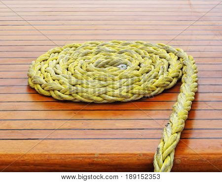 Close-up of a rope with a knotted end tied around a cleat on a wooden pier/ Nautical rope