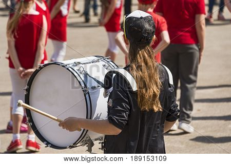 Girl drummer  with  baseball cap and big drum
