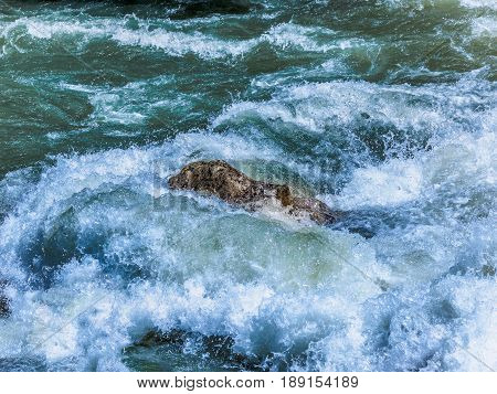 Mountain river with wild rapids water breaks violently over a rock