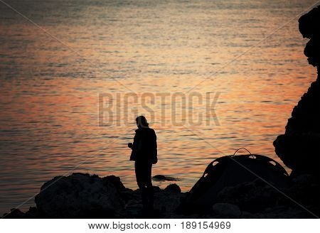 Silhouette of trekker on rocky seashore near camping tent on overnight stay at summer sunset