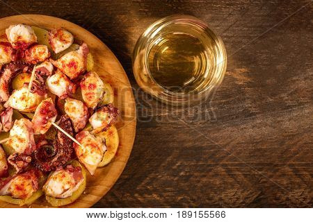 An overhead photo of pulpo a la gallega, an octopus with boiled potatoes, typical Spanish Galician dish, on a traditional wooden plate, with a glass of white wine and copy space