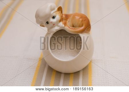 Porcelain jar for salts with a figure of a reclining kitty chef filled with coarse salt