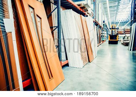 Warehouse of entrance and interior doors. Shelf with structural materials on the shelves in the construction warehouse. Concept logistics companies and large  warehouse industrial