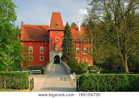 View on beautiful traditional european antique red castle Cervena Lhota with bridge. Famous Czech Republic Renaissance castles. Red castle among green forest and pond. Famous sightseeing tours