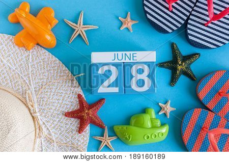 June 28th. Image of june 28 calendar on blue background with summer beach, traveler outfit and accessories. Summer time.