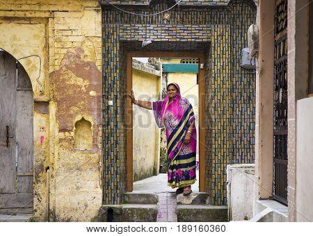 HARIDWAR, INDIA - MARCH 23, 2014: indian woman wearing colourful sari In the doorway