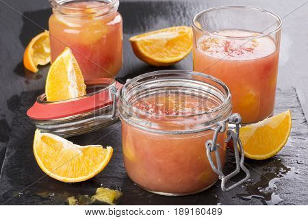 Citrus jelly in a glass jar on a black slate background. Homemade grapefruit orange gelatin dessert. Healthy low fat and low calorie meal.