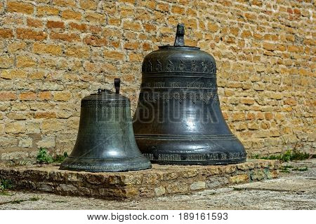 Ancient bells on a stone pedestal against the background of the Narva castle wall in the city of Narva.