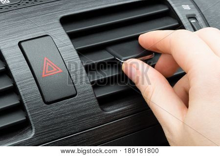 Driver hand tuning air ventilation grille with power regulator; Emergency flasher switch on the panel; modern car interior detail