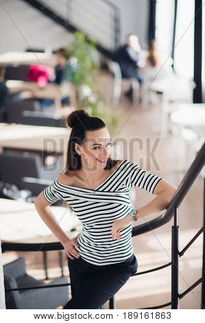 Portrait of young brunette woman posing for camera in a cafeteria while looking away