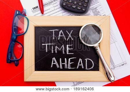 Tax Time - USA - wooden letters with 1040 Tax Form, magnifying glass and eyeglasses