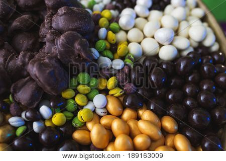 Assorted from a variety of different sweets in the glaze of white and dark chocolate, in the sugar glaze. Candy and dessert for guests at the event. Light snacks and refreshments. Soft focus.