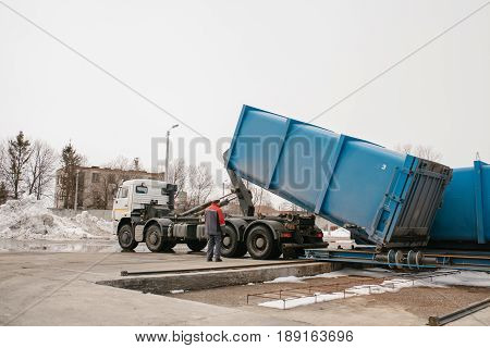 Loading container with waste to a special machine for subsequent transportation to a waste disposal plant. Waste processing plant. Business for sorting and processing of waste. Cargo.