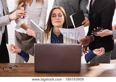 Young Businesswoman Surrounded By Hands That Give Her A Lot Of Work In Office