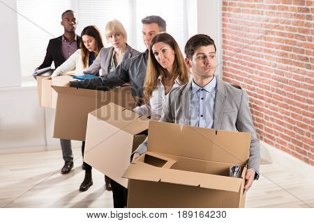 Row Of Diverse Businesspeople Standing With Cardboard Boxes In Office