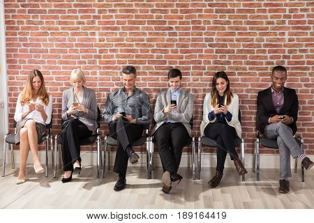 Row Of Diverse People Waiting For Job Interview Using Cell Phone In Office