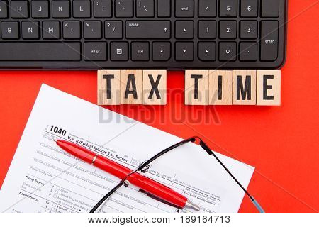 Tax Time - USA - wooden letters with 1040 Tax Form, eyeglasses and keyboard