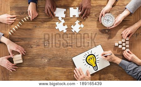 Businesspeople Planning A Strategy In Business Each Holding Different Important Metaphorical Element