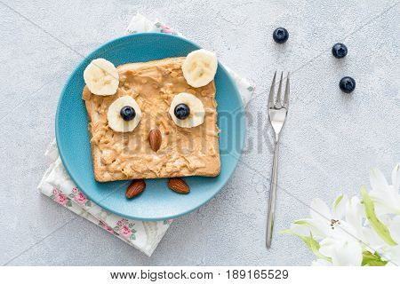 Peanut butter toast with banana, almonds and blueberries on a blue plate shaped as cute little owl. Breakfast for kids, food art concept