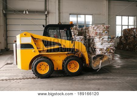 An industrial machine is driving through the plant. Waste processing plant. Recycling and storage of waste for further disposal.