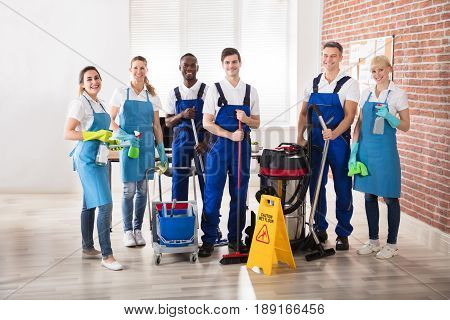 Portrait Of Happy Diverse Janitors In The Office With Cleaning Equipments