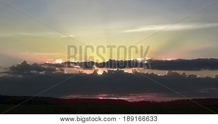 beautiful sky with shaft of sunlight and clouds during sunset and forest in spring