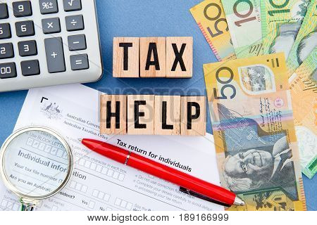 Tax Help - Australia - wooden letters with tax form, magnifying glass, money and calculator