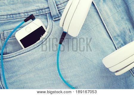 Smartphone in blue jeans pocket with wired white headphones; Listen to music from your phone; Vintage filter