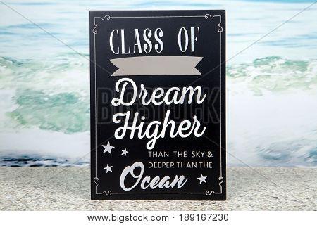 A graduation sign against an ocean background