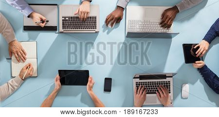 Overhead View Of Businesspeople's Hand On Desk With Laptop And Digital Tablet In Office