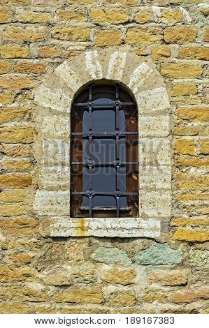 Window with an arch on the background of the wall of the old fortress of yellow limestone in the city of Narva.