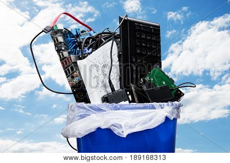 Close-up Of Damaged Hardware Equipment In Blue Dustbin Against Sky