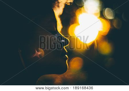 True tilt-shift side view silhouette of beautiful curly Brazilian lady backlighted by stunning orange sunset with strong bokeh and chroma hoop with copy space place for text logo or your advertising poster