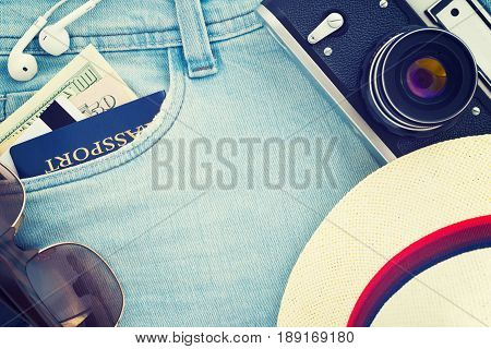 Passport dollar banknotes credit card headphones sunglasses hat retro film photo camera on jeans. Travel top view background; Vacation suite. Vintage filter