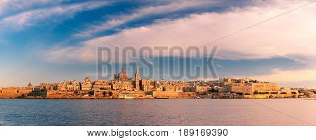 Panoramic view of Valletta Skylineat at beautiful sunset from Sliema with churches of Our Lady of Mount Carmel and St. Paul's Anglican Pro-Cathedral, Valletta, Capital city of Malta