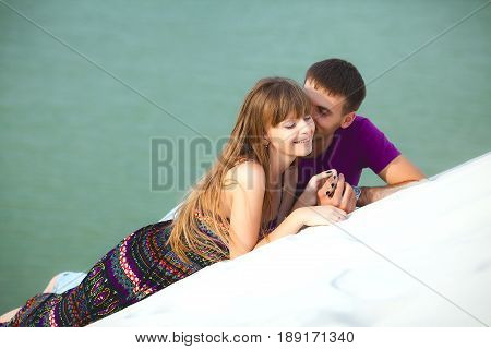 Lovers lying on the barkhan over ocean. romantic travel honeymoon vacation summer holidays. young girl dressed in a colorful dress and man in a violet t-shirt