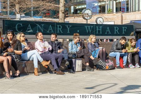 London UK - May 10 2017 - Outdoor space in Canary Wharf packed with people sitting and enjoying the sunny day