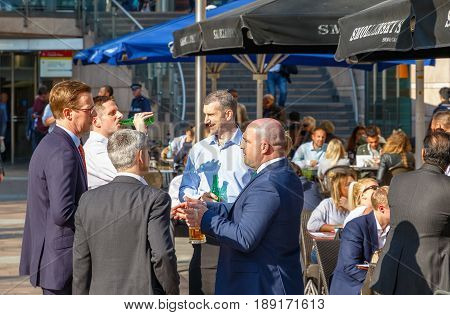 Group Of Businessmen Drinking At A Outdoor Bar In Canary Wharf