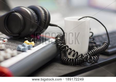 Closeup of coffee cup and headphones with spiral cord in radio studio