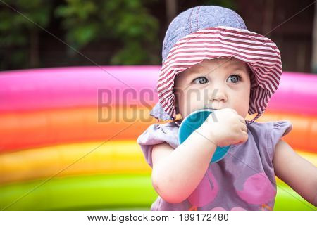 Beautiful baby girl playing in playpen with toys in the park