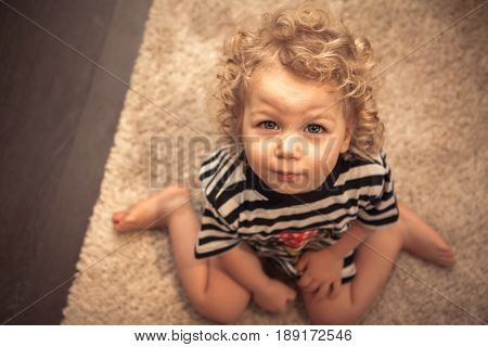 Entreating cute curly baby girl sitting on floor and looking at camera with view from above