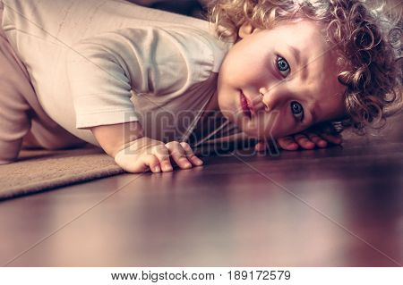 Scared child hiding under the bed in kid room and looking scared