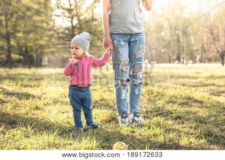 Child with mother standing together with holding hands in summer park on grass. Main subject is child. Unrecognizable mother on photo.  Concept for togetherness and care.