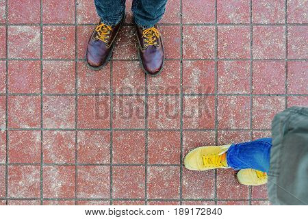 Red brick paving stones on a sidewalk with legs of two people. Abstract background texture. Date concept