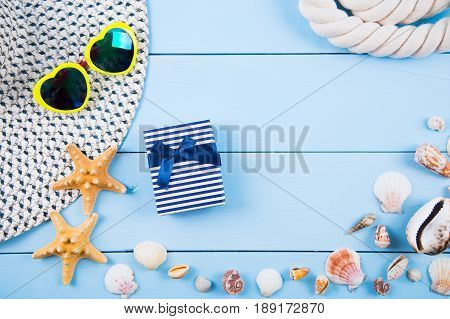 Hat and yellow sunglasses in shape of heart with shells starfishes gift box and sea rope on blue wooden background. Summer marine background. Beach accessories flat lay with negative space.