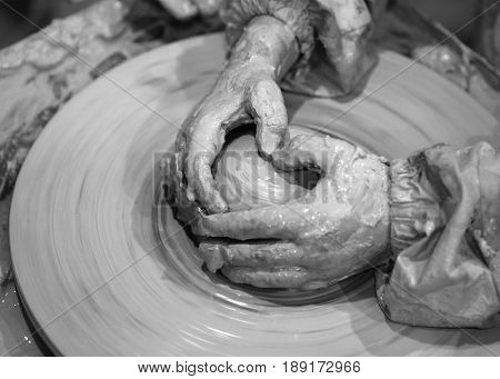 Black And White Hands Of Young Girl In Process Of Making Clay Bowl On Pottery Wheel