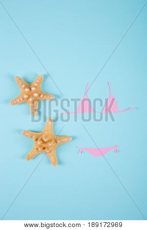 Pink Paper Bikini Swimsuit With Two Starfishes On Blue Background. Minimalistic Summer Flat Lay.