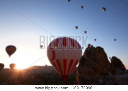 Blurred View On Hot Air Balloons And Blue Clear Sunlight Sky And Fairy Chimneys Rock Formations