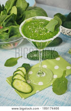 Martini glass filled with fresh green spinach and cucumber smoothie on light blue wooden background. Non-alcoholic drinks. Healthy food and vegetarian concept.